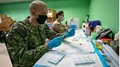 Military personnel wearing face mask getting people ready for the COVID-19 vaccine