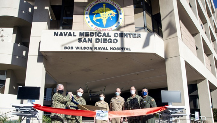 Military personnel wearing face mask standing in front of the Naval Medical Center in San Diego cutting a red ribbon