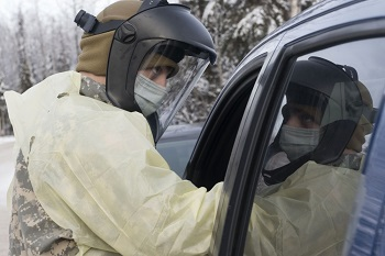 Healthcare worker, wearing personal protective gear, leans into a car at a pharmacy drive-thru