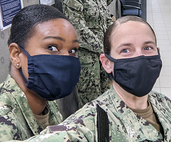 Two soldiers, wearing masks, taking a selfie