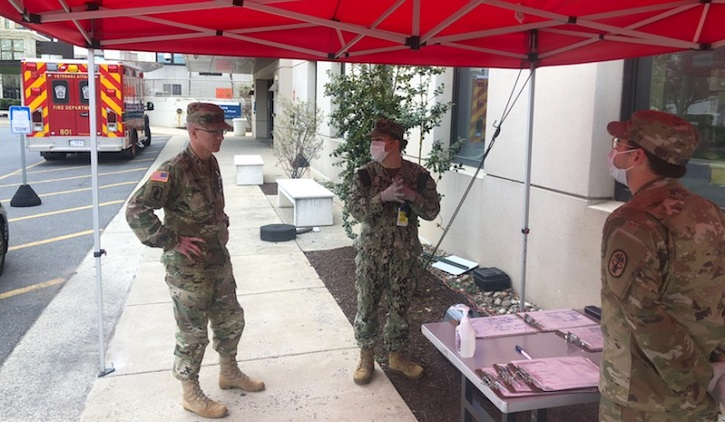 Army Lt. Gen. Ron Place and two soldiers stand at a table with COVID-19 testing supplies