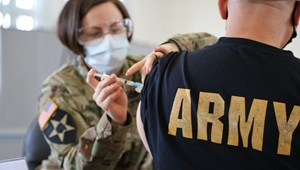 Military health personnel wearing a face mask giving someone the COVID-19 Vaccine