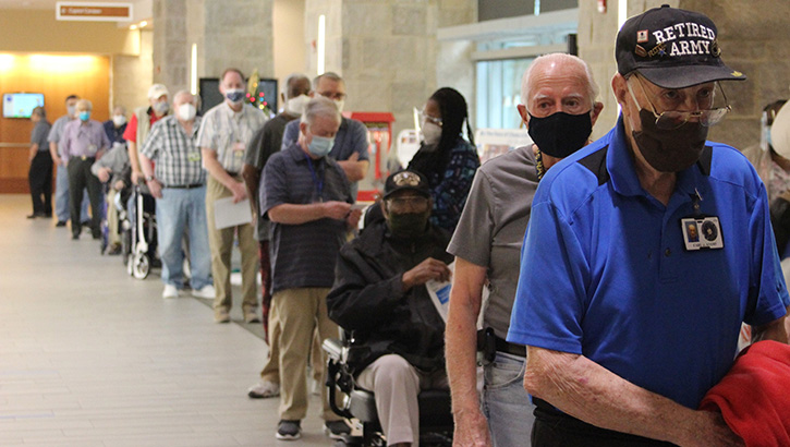 Nursing home members, wearing masks, wait in a line to get their COVID vaccine