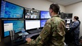 Uniformed service member stands behind wall of computer screens