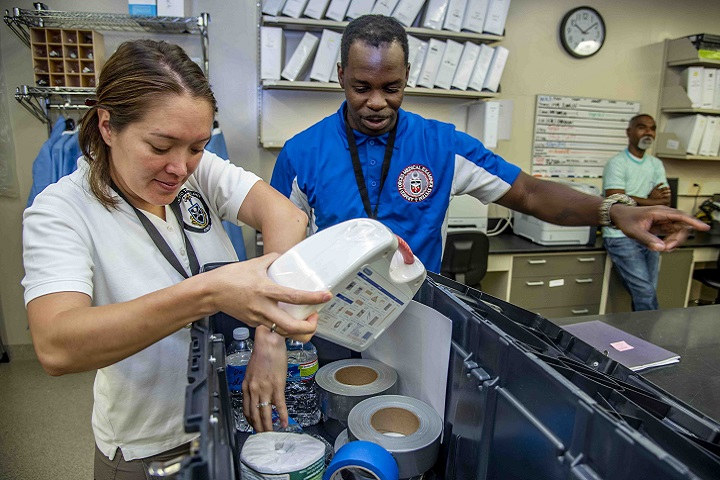 Air Force Tech Sgt. Aisuluu Alford (left) and Army Staff Sgt. Joseph Tutt, both Armed Forces Medical Examiner System forensic toxicology laboratory technicians, grab supplies out of the Shelter-In-Place Kit during a Shelter-In-Place exercise. The exercise was part of Safe and Sound week where AFMES personnel were able to engage in different safety activities. (U.S. Air Force photo by Staff Sgt. Nicole Leidholm)