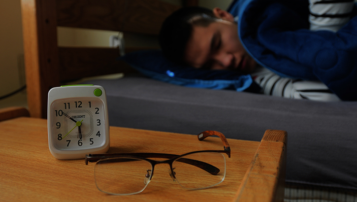 Man sleeping in bed with alarm clock on side table