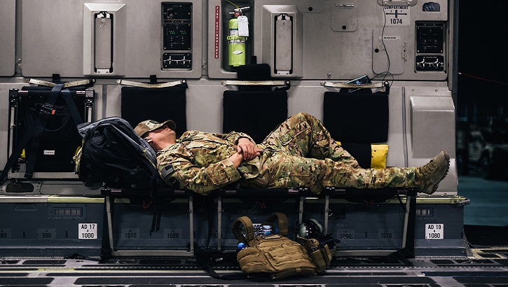 An Air Force Airman sleeps inside a C-17 Globemaster III during a flight over an undisclosed location in support of Operation Freedom Sentinel. (U.S. Air Force photo illustration)