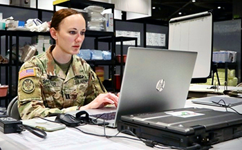 Military personnel typing on a laptop in an office