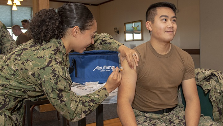Hospital Corpsman administers a flu shot to a navy officer.