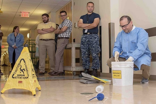 Mike Ende, Armed Forces Medical Examiner System forensic toxicology inventory manager, demonstrates proper techniques for cleaning up a spill to AFMES forensic toxicology personnel during Safe and Sound Week. Safe and Sound Week is a nationwide campaign to raise awareness and understanding of safety and health programs within the workplace. (U.S. Air Force photo by Staff Sgt. Nicole Leidholm)