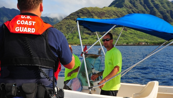 Image of Coast Guard employee talking with man on boat