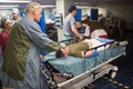 Navy Lt. Cmdr. Arthur Lammers, an anesthesiologist assigned to the hospital ship USNS Comfort, practices patient transfer during a mass casualty exercise. (U.S. Army photo by Spc. Joseph DeLuco)