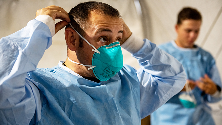 Man putting on PPE, including a mask