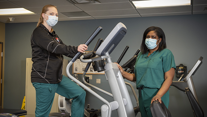 Two military personnel wearing face mask standing on gym equipment