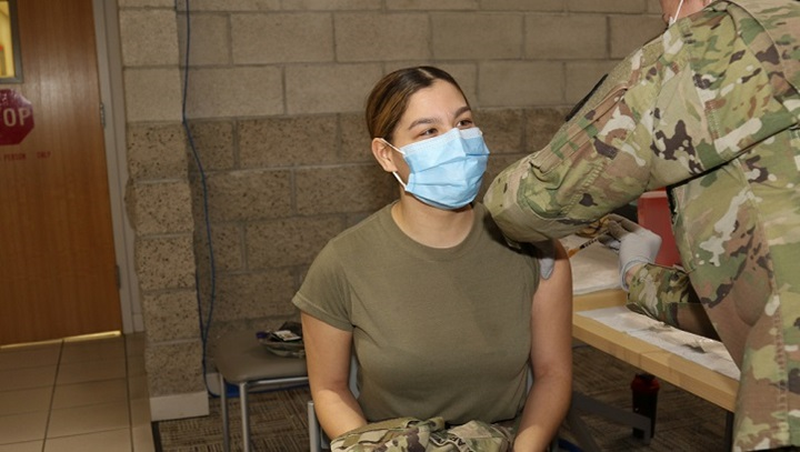 Image of soldier getting a vaccine in her left arm