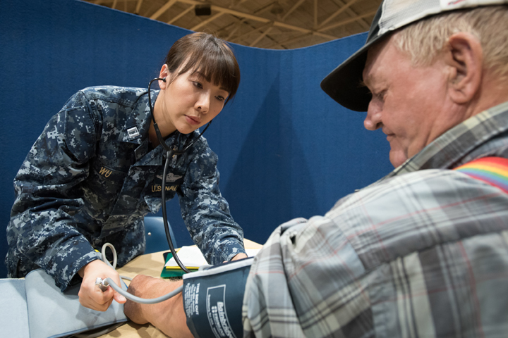 Navy Lt. Xin Wu, a nurse from Expeditionary Medical Facility Bethesda in Maryland, checks a patient's blood pressure at a health care clinic set up by the Air Guard and Navy Reserve at a high school in Beattyville, Kentucky. The clinic was part of a mission to train military medical personnel while offering free health care to Eastern Kentucky residents. (U.S. Air Force photo by Lt. Col. Dale Greer)