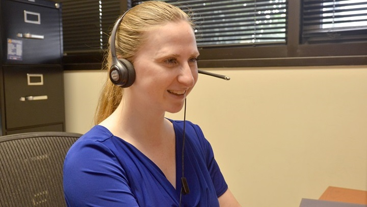 Image of smiling woman with telephone headset sitting at her desk