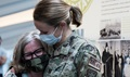 Military health personnel wearing face masks hugging