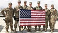 Seven soldiers standing behind an American flag