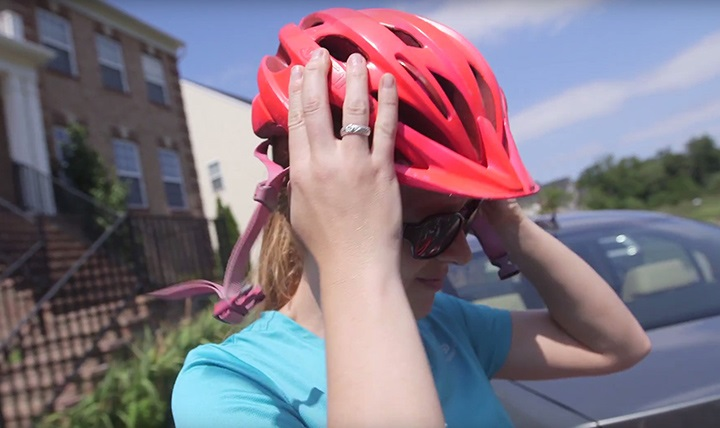 Woman putting on bike helmet